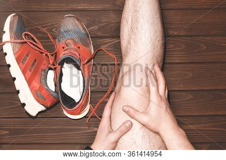 Young Sport Man With Strong Athletic Legs Holding Knee With His Hands. In Pain After Suffering Ligam