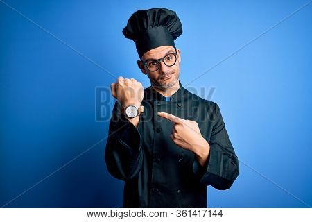 Young handsome chef man wearing cooker uniform and hat over isolated blue background In hurry pointing to watch time, impatience, looking at the camera with relaxed expression