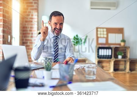 Middle age handsome businessman wearing tie sitting using laptop at the office pointing finger up with successful idea. Exited and happy. Number one.