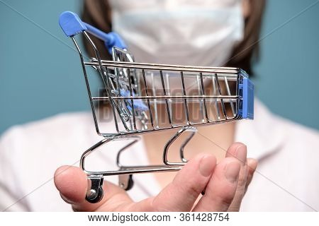 Decorative Shopping Trolley In Hand, On The Background Of The Face In A Medical Mask. Concept Of Cri