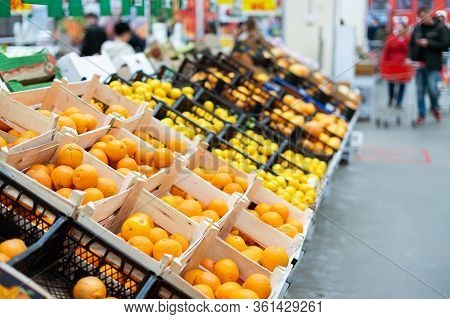 Bright Fresh Oranges And Lemons In Baskets In A Supermarket