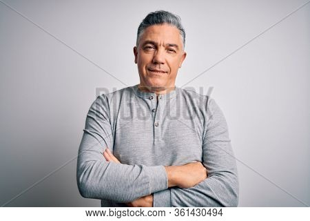 Middle age handsome grey-haired man wearing casual t-shirt over white background happy face smiling with crossed arms looking at the camera. Positive person.