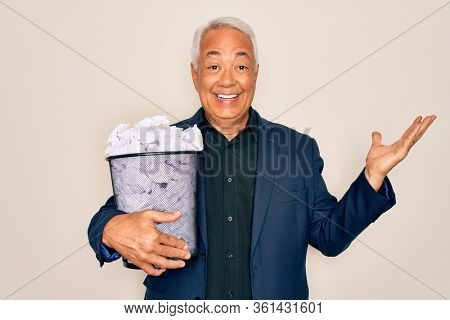 Middle age senior grey-haired business man holding paper bin full of rubbish documents very happy and excited, winner expression celebrating victory screaming with big smile and raised hands