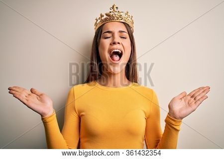 Young beautiful brunette woman wearing golden queen crown over white background celebrating mad and crazy for success with arms raised and closed eyes screaming excited. Winner concept
