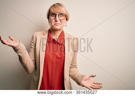 Young blonde business woman with short hair wearing glasses and elegant jacket clueless and confused expression with arms and hands raised. Doubt concept.