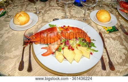 Festive Table Set With Dish Of Huge Grilled Lobster And Vegetable.