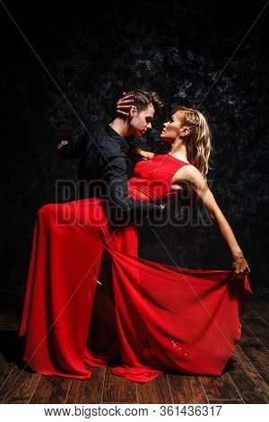 passion and love concept. young couple in elegant evening dresses dancing in the roome filled with dramatic light