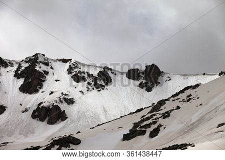 Rocks With Snow Cornice And Traces From Avalanche. High Snowy Mountains And Cloudy Sky In Gray Day.