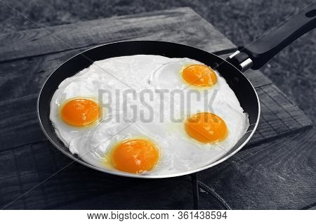 Black And White Old Wooden Table And Frying Pan With Fried Eggs On Camping Gas Stove. Outdoor Cookin