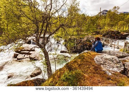 Travel And Hiking. Tourist Woman Taking Photo With Camera, Enjoying Waterfall Torrential River Along
