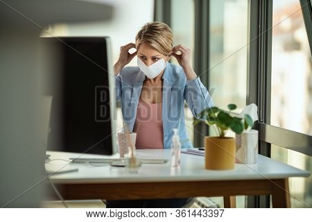 Business Woman In A Medical Protective Mask Works At The Computer During Self-isolation And Quaranti