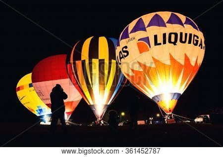Mondovì, Italy - January 5, 2019: Night Show Of Hot-air Balloons, With Photographers On Foreground,