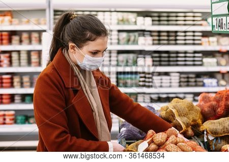 Pretty Woman In Protective Mask Chooses Vegetables At The Grocery Store. Shopping During An Epidemic