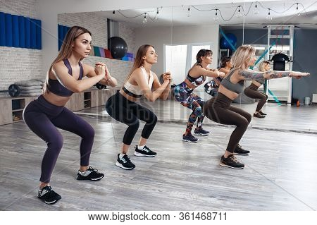Group Of Four Young Fit Girls Doing Weight Loss Workout In Fitness Class. Sport, Fitness And Lifesty