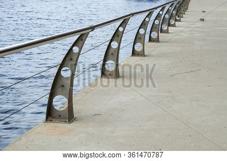 Fragment Of River Embankment With Concrete Pavement, Modern Metal Balustrade With Steel Handrails An
