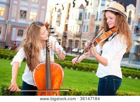 Two Women Strings Duet Playing Violin And Cello In Square