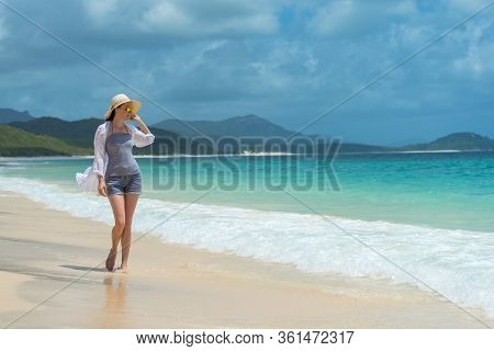 Woman In A Sun Hat And Sunglasses On The Tropical Beach With Mountains In The Distance. Whitsunday I