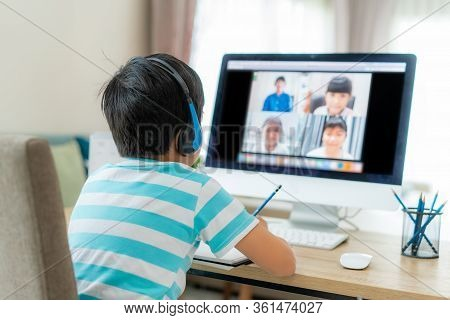 Asian Boy Student Video Conference E-learning With Teacher And Classmates On Computer In Living Room