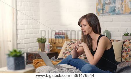 Casual woman sitting on bed working online from home with laptop computer. Stay at home and work in home office.