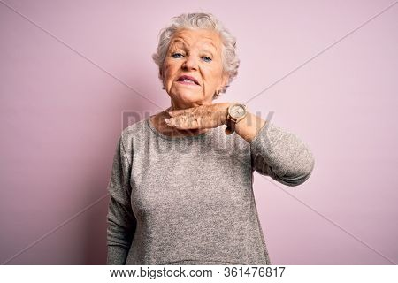 Senior beautiful woman wearing casual t-shirt standing over isolated pink background cutting throat with hand as knife, threaten aggression with furious violence