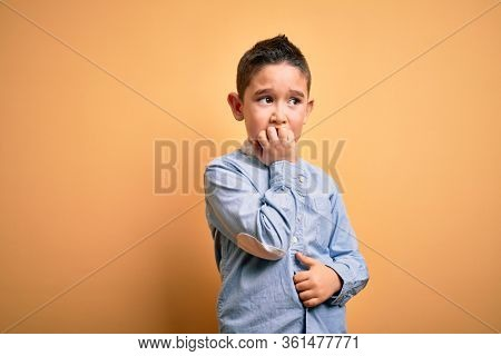 Young little boy kid wearing elegant shirt standing over yellow isolated background looking stressed and nervous with hands on mouth biting nails. Anxiety problem.