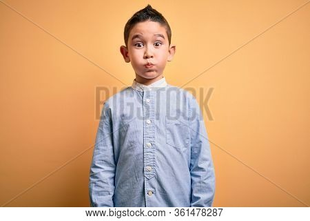 Young little boy kid wearing elegant shirt standing over yellow isolated background puffing cheeks with funny face. Mouth inflated with air, crazy expression.