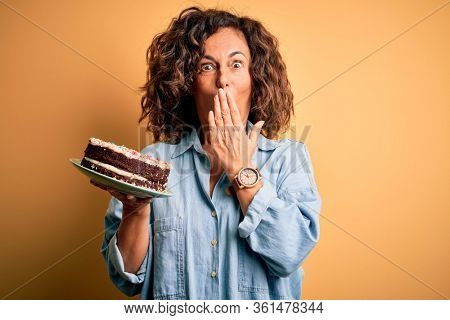 Middle age beautiful woman holding cake standing over isolated yellow background cover mouth with hand shocked with shame for mistake, expression of fear, scared in silence, secret concept