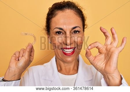 Middle age senior dentist woman holding clear aligner for teeth correction doing ok sign with fingers, excellent symbol