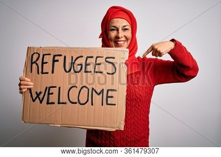 Woman wearing muslim hijab asking for immigration holding welcome refugees message with surprise face pointing finger to himself