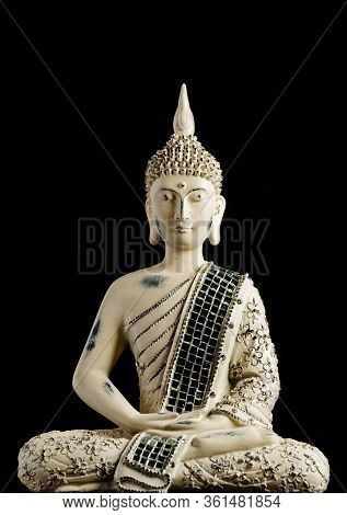 A Small Replica Statue Of The Buddha Against A Black Background