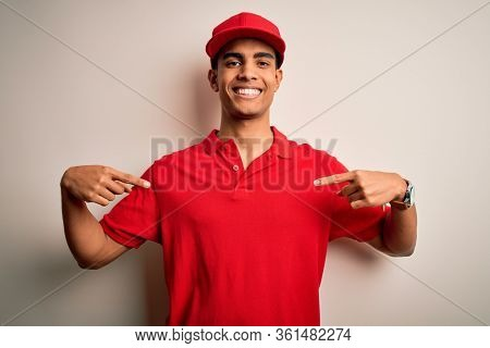 Young handsome african american man wearing casual polo and cap over red background looking confident with smile on face, pointing oneself with fingers proud and happy.