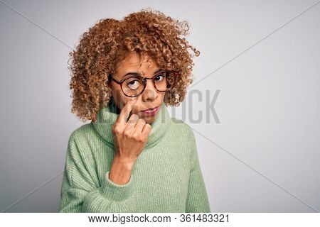 Young beautiful african american woman wearing turtleneck sweater and glasses Pointing to the eye watching you gesture, suspicious expression