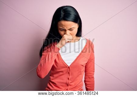 Young beautiful chinese woman wearing casual sweater over isolated pink background feeling unwell and coughing as symptom for cold or bronchitis. Health care concept.