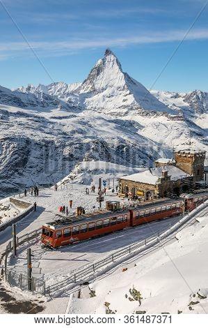 Gornergrat, Zermatt, Switzerland - November 12, 2019: Red Cable Car Train On Snowy Railway At Summit