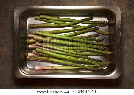 Wild asparagus on a metal tray.