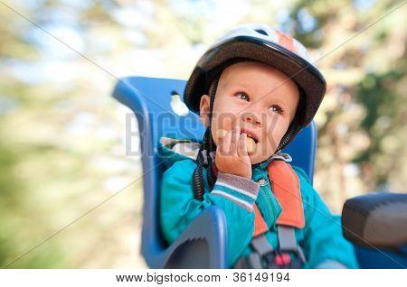 Little Boy In Bike Child Seat Eating Cracker