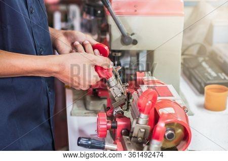 Locksmith In Workshop Makes New Key. Professional Making Key In Locksmith. Machine Production Of Dup