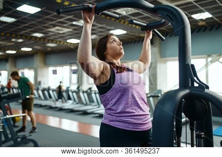 Overweight woman on exercise machine in gym