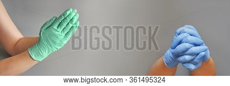 Hands Clasped In Blue And Mint Glove. Grey Background