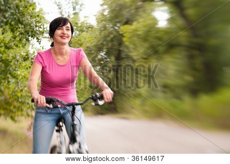 Woman Riding Bike On The Summer Forest Road. Lensbaby Effect