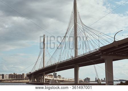 Modern Cable Stayed Bridge Over The River Against Cloudy Sky. Engineering Construction Closeup
