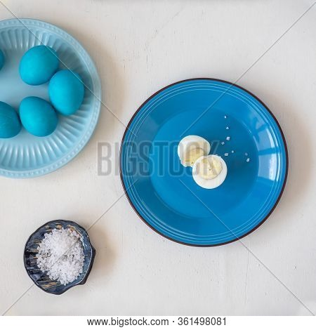 Easter Blue Eggs On Two Ceramic Plates In Blue Tones On A White Wooden Table