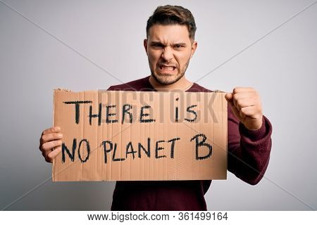 Young activist man holding protest banner for climate change and environment change annoyed and frustrated shouting with anger, crazy and yelling with raised hand, anger concept