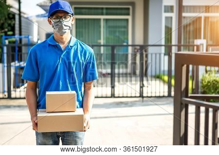 Asian Delivery Man Wearing Mask Delivers Parcel, Customer In Medical Gloves Signs On Tablet. Deliver
