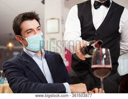 Waiter pouring wine to a masked customer, funny coronavirus concept