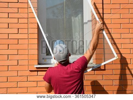 A Worker Is Installing A Window Mosquito Net, Fly Screen Or Insects Screen To Protect The House From