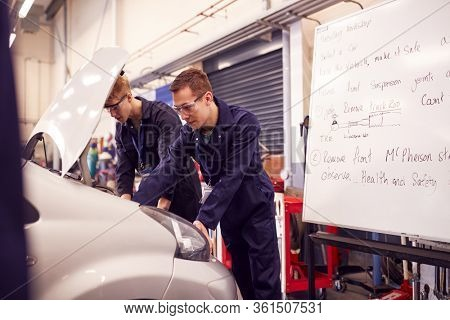 Two Male Students Studying For Auto Mechanic Apprenticeship At College Working On Car Engine
