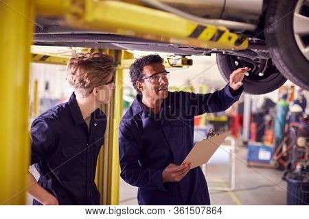Male Tutor With Student Looking Underneath Car On Hydraulic Ramp On Auto Mechanic Course