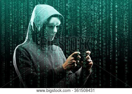 Computer Hacker In Mask And Hoodie Over Abstract Binary Background. Obscured Dark Face. Data Thief,