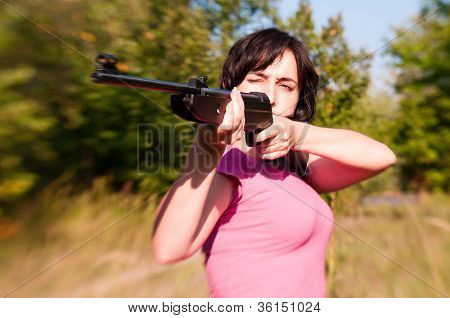 Woman Aiming Rifle In The Summer Forest. Lensbaby Effect